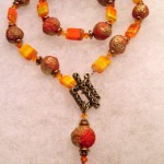 These rounded gold/orange textured beads were made from barkcloth, a source that is plentiful in Uganda. Czeck glass, Swarovksi crystal and orange agate create a unique textured look. Finished in the front for extra dangle factor!!
